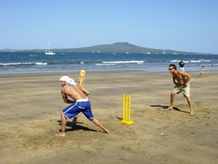 Beach cricket, Rangitoto in the background.